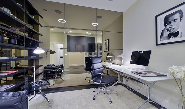 Modern home office with floor to ceiling mirror wall, situated in the basement of this 4 bedroom Chelsea townhouse