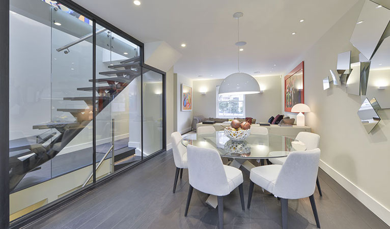 Kitchen glazed wall, self-supporting staircase, open plan seating & dining room in Chelsea SW7
